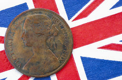 Queen Victoria one penny British flag. One penny copper coin with an image of queen Victoria from 1864 on a British flag background. This coin has been in royalty free stock photography