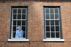 Queen in window. Full size photograph of Queen Elizabeth II in a window of old red-brick building, taken in York, Yorkshire, England stock images