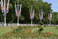 Queens Gardens. London. England. British Union Flags around the Queens Gardens outside Buckingham Palace. Westminster. London. England. With tourists Royalty Free Stock Images
