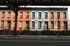 Queens Row Houses. Colorful row houses in Queens, New York, under the subway tracks royalty free stock photo