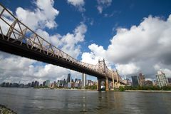 Queensboro bridge over the river and buildings in Manhattan with cloudy sky Royalty Free Stock Photos