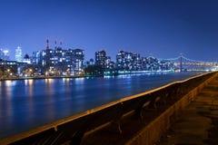 Queensboro Bridge- und Queensskyline durch den East River, nachts, New York City, USA stockfotografie