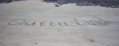 Queensland som är skriftlig i sanden royaltyfri fotografi