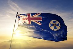 Queensland state of Australia flag textile cloth fabric waving on the top sunrise mist fog. Beautiful royalty free stock photo