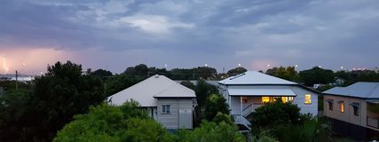 Queenslander homes in summer storm and lightening. Queenslander homes in summer storm with low clouds and lightening strike Stock Images