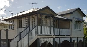 Queenslander and verandah with lattice. Queenslander home in cream, white with lattice, stairs, window shades and ornate fretwork Stock Image