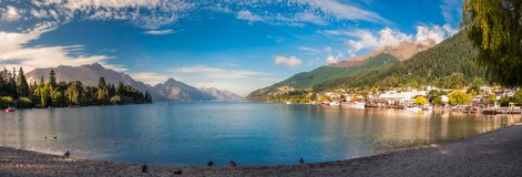 Queenstown Bay Panorama, New Zealand. Early morning at the beach on lake Wakatipu in Queenstown, New Zealand, with the wharf on the right hand side, Queenstown Royalty Free Stock Image