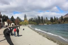 Queenstown lake Wakatipu, New Zealand, people at beach. New Zealand landscape, mountains and a lake, forest, nature on the south island. Queenstown is located on royalty free stock photos