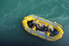Bungee jumper rescue boat. Queenstown, New Zealand - September 23, 2017 : Bungy`s crew on rubber boat grab the jumper into the boat after bungy jump from the Royalty Free Stock Photography