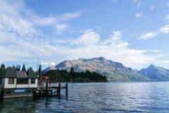 Queentown/新西兰- 2017年12月2日:浇灌观测所办公室和小船港口在湖边在晴天 免版税库存照片