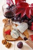 Queijo azul francês, uvas vermelhas, escarlate das folhas e copo de vinho Fotografia de Stock Royalty Free