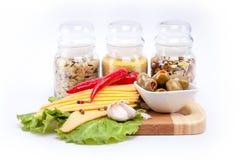 Queijo, cereais diferentes em uns frascos, azeitonas e pimenta imagem de stock royalty free
