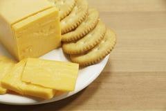 Queijo cheddar e biscoitos na placa Imagens de Stock Royalty Free