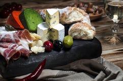Queijo da mistura no fundo escuro na placa de madeira com uvas, mel, porcas, tomates e manjericão Vista superior imagem de stock royalty free