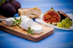Queijo de cabra com figos e as uvas maduros Fotos de Stock Royalty Free