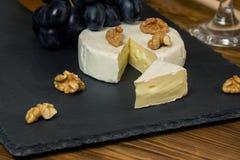 Queijo do camembert em uma bandeja escura ao lado das porcas e do mel azuis doces das uvas fotos de stock royalty free