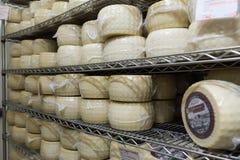 Queijo do leite de vaca, armazenado no prateleiras de madeira e deixado para amadurecer a Fotos de Stock