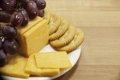 Queijo e biscoitos com as uvas na placa Foto de Stock