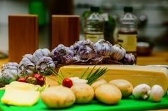 Queijo e ingredientes para preparar o alimento em uma tabela de madeira imagem de stock