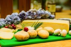 Queijo e ingredientes para preparar o alimento em uma tabela de madeira imagens de stock royalty free
