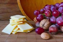 Queijo e uvas em uma placa Fotos de Stock Royalty Free