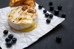 Queijo grelhado do camembert no papel com brindes, mirtilos e nozes na tabela preta, close up fotos de stock