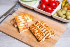 Queijo grelhado do haloumi em uma placa de madeira com azeitonas, cereja, pepinos e pepperoni foto de stock
