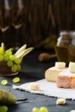 Queijo macio francês da região de Brittany e brie cortado com pera, as uvas verdes, o mel e os vidros do vinho branco Fotografia de Stock Royalty Free
