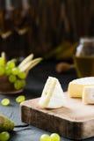 Queijo macio francês da região de Normandy cortado com uvas, a pera, mel e vidros verdes do vinho Fotografia de Stock