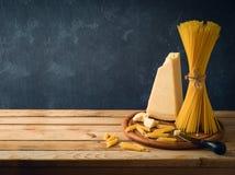 Queijo parmesão, espaguetes e massa na tabela de madeira imagem de stock