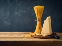 Queijo parmesão, espaguetes e massa na tabela de madeira imagens de stock royalty free