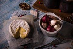 Queijo quente do camembert na placa de madeira com alho e cebola Fotos de Stock