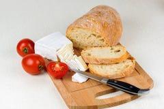Queijo, tomates e pão cortados para o café da manhã em uma placa Fotografia de Stock Royalty Free