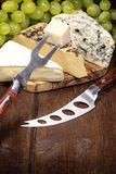 Queijo, uvas do vinho branco, faca e forquilha Imagem de Stock