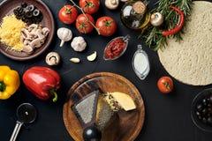 Queijo, vegetais diferentes na tabela preta Ingredientes para a pizza italiana tradicional Imagem de Stock