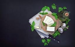 Queijo, verdes e especiarias em um fundo escuro Fundo do alimento imagens de stock