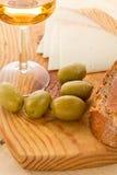 Queijo, vinho branco, azeitonas, pão Imagem de Stock