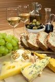 Queijo, vinho branco, uvas, azeitonas, pão Fotografia de Stock