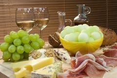 Queijo, vinho, uvas, presunto de Parma do pão & melão Imagem de Stock Royalty Free