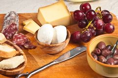 Queijos, carnes e uvas para emparelhar-se em uma degustação de vinhos Foto de Stock Royalty Free