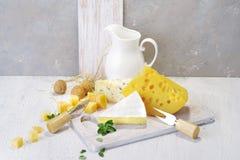 Queijos e leite em uma placa idosa clara Vista rústica Fotografia de Stock