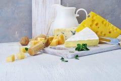 Queijos e leite em uma placa idosa clara Vista rústica Fotografia de Stock Royalty Free