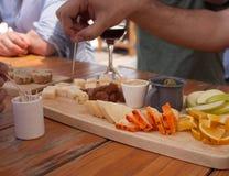 Queijos perto de mim a provar com pão, vinho, frutos, azeitonas, e mel fotos de stock royalty free