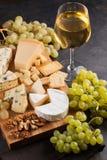 Queijos sortidos com uvas brancas, nozes, biscoitos e vinho branco em uma placa de madeira Alimento por uma data romântica em uma fotografia de stock royalty free