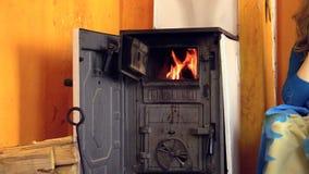 A queimadura da chama do fogo no fogão e na mulher rurais leu o livro Zumbido para fora video estoque