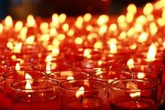 Queimadura de muitas velas do vermelho Fotografia de Stock Royalty Free