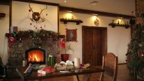 Queimadura do fogo em uma chaminé decorada com luzes, grinalda, meias e presentes da festão na Noite de Natal Presentes e vídeos de arquivo