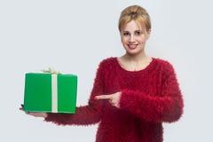 Queira-o? Retrato da jovem mulher feliz na blusa vermelha que está e que guarda a caixa de presente verde e que aponta o dedo, ol foto de stock royalty free
