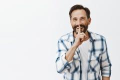 Queira ouvir o segredo Retrato do homem adulto considerável entusiasmado com barba e do bigode que sorriem alegremente ao fazer c foto de stock