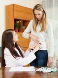 Queixa da mulher da dor no lado ao doutor Imagem de Stock
